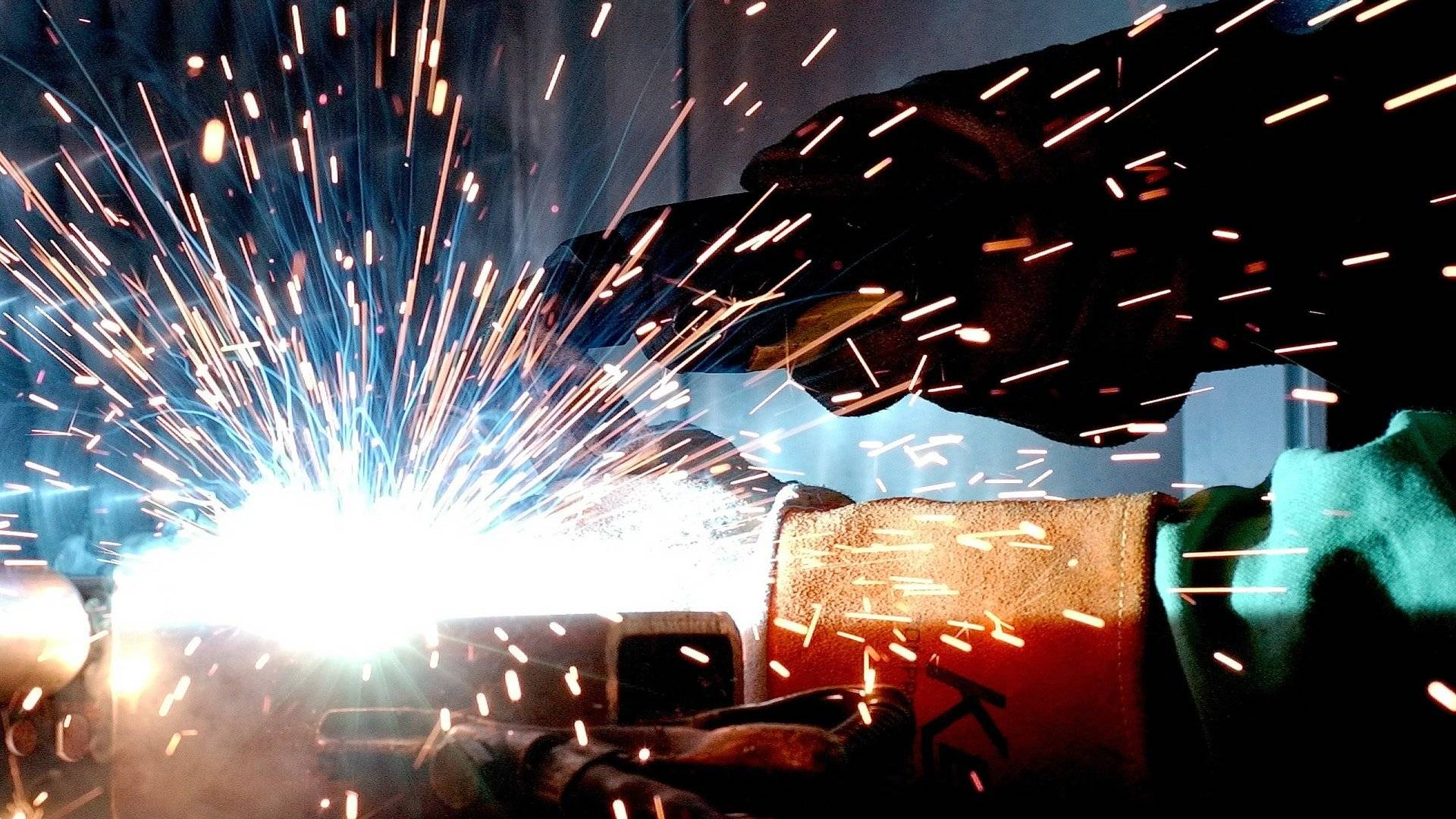 person in welding mask close to weld causes sparks