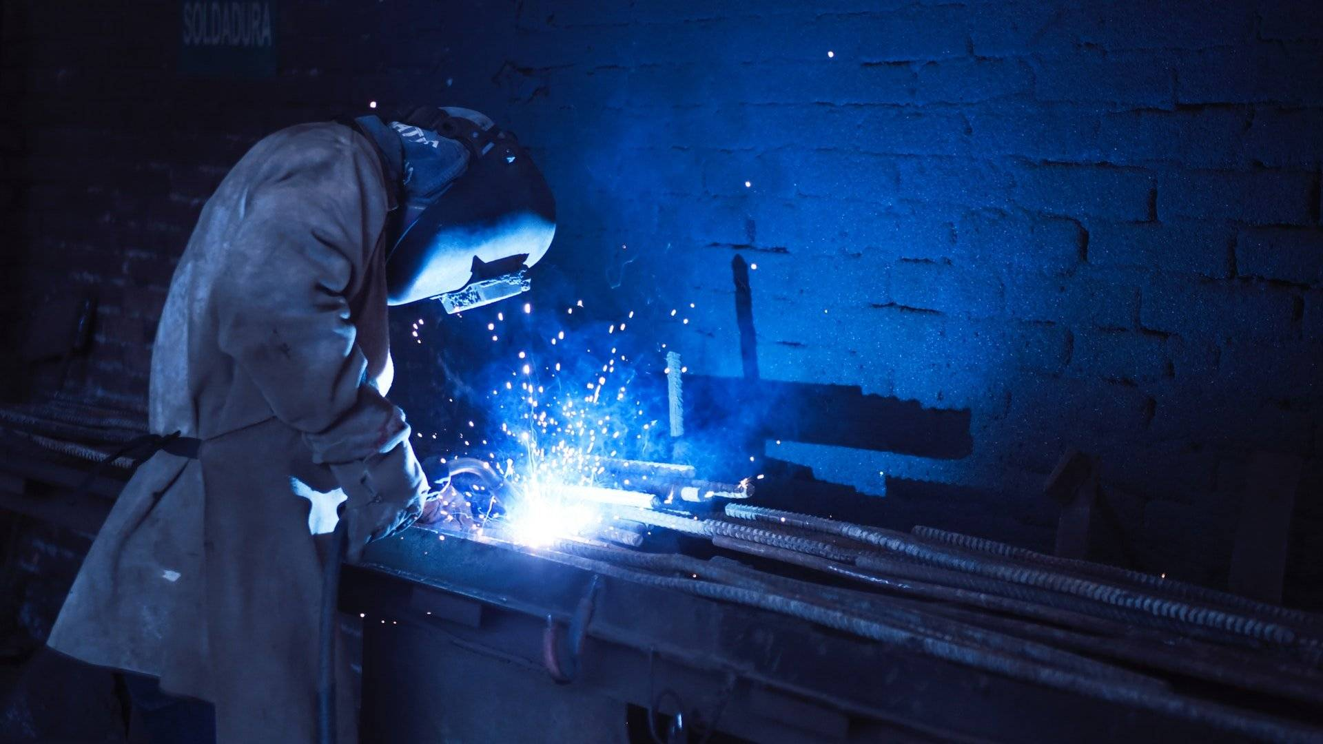 person with welding mask welds steel rods