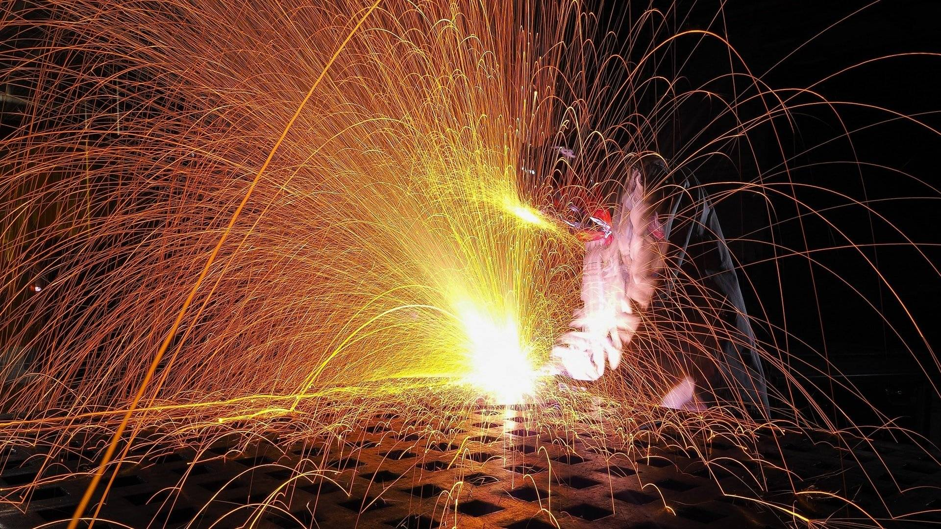 shower of sparks from person welding in welding mask
